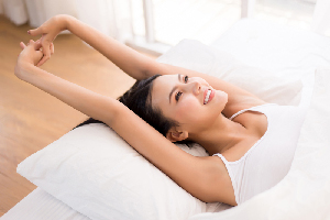 Beautiful asian woman stretching and waking up in her bedroom at the morning,Happy and smiling