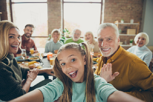 Video call from happy big family celebrate thanksgiving day october, autumn event party small little girl kid make selfie mature grandfather say hi wave hand grandmother enjoy meal in house