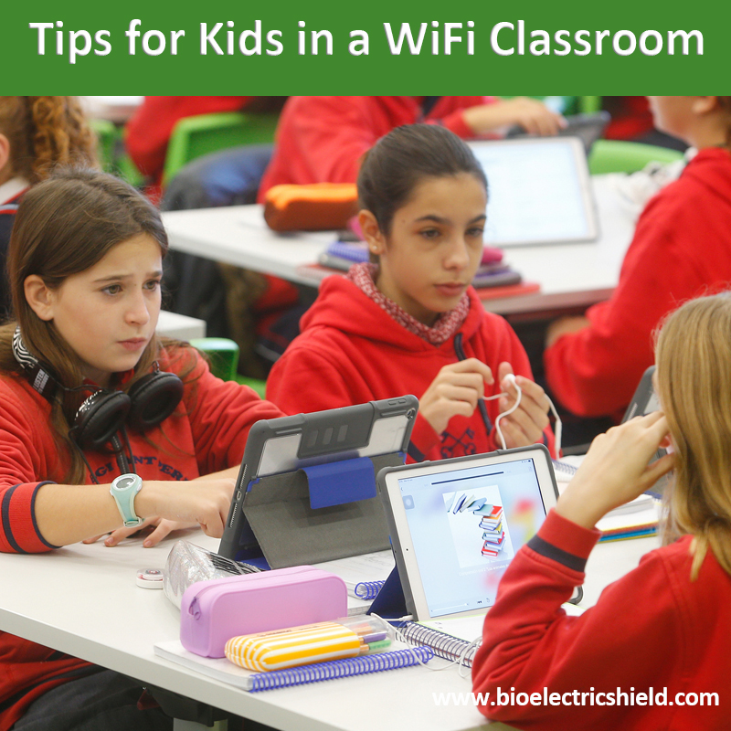 Photo of kids in class with laptops and cellphones wifi in classroom